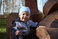 Een klein kind klampt zich aan houten logboeken van de het glimlachen zomer in het Park vast royalty-vrije stock afbeelding