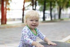 Een klein kind leert om dichtbij de banken, peuter te lopen Royalty-vrije Stock Foto
