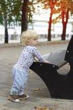 Een klein kind leert om dichtbij de banken, peuter te lopen Stock Foto's