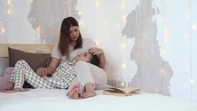 Een klein kind ligt op zijn moeder` s overlapping Het mamma strijkt zijn zoon op het hoofd en glimlacht zitting op het bed stock video