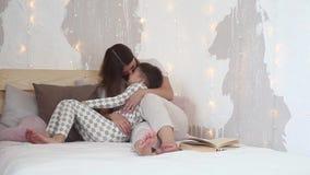 Een klein kind ligt op zijn moeder` s overlapping Het mamma strijkt zijn zoon op het hoofd en glimlacht zitting op het bed Langza stock video