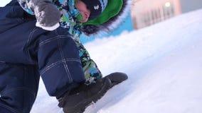 Een klein kind loopt in het de winterpark De speel en glimlachende baby beklimt op de heuvel, die opnieuw stijgingen vallen Actie stock video