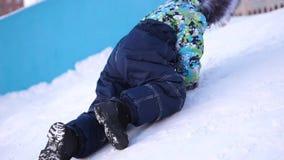 Een klein kind loopt in het de winterpark De speel en glimlachende baby beklimt op de heuvel, die opnieuw stijgingen vallen Actie stock videobeelden