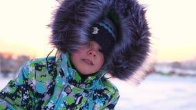 Een klein kind loopt in het de winterpark Speel en glimlachende baby op witte pluizige sneeuw De close-up van het gezicht Actieve stock footage