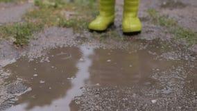 Een klein kind schoeide in rubberlaarzen, springend in een vuile vulklei na de regen stock video