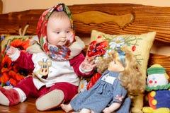 Een klein kind in een sjaalzitting op een bank met geborduurde hoofdkussens stock afbeelding