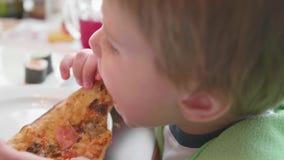 Een klein kind in een snel voedselkoffie eet pizza pizza met kaas, ham, tomaten en kruiden in de schotel op witte achtergrond stock videobeelden