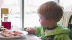Een klein kind in een snel voedselkoffie eet pizza pizza met kaas, ham, tomaten en kruiden in de schotel op witte achtergrond stock video