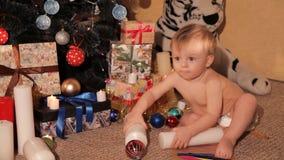 Een klein kind speelt dichtbij een Kerstboom stock footage