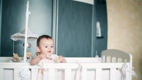 Een klein kind spuugt uit de fopspeen die in de voederbak HD opstaan stock video