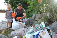 Een klein kind verzamelt afval op het strand Zijn papa richt zijn vinger waar te om huisvuil te werpen De ouders onderwijzen kind royalty-vrije stock afbeelding