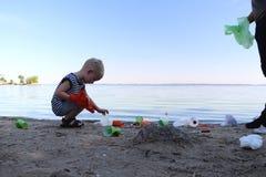 Een klein kind verzamelt afval op het strand Zijn papa richt zijn vinger waar te om huisvuil te werpen De ouders onderwijzen kind royalty-vrije stock afbeeldingen