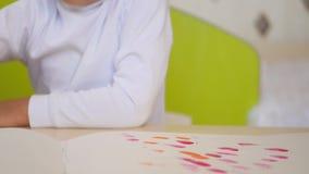 Een klein kind zet zijn vinger in de verf en smeert het beeld op een blad van document in close-up De ontwikkeling van a stock video