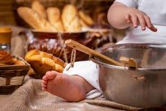 Een klein kind zit op een houten lijst en ontwikkelt het deeg met een deegrol, is de bloem rond verspreid en het brood ligt E stock foto