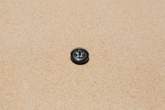 Een klein Kompas, strand, zand, ronde, het noorden, zuiden, het oosten, het westen, rood, zwarte, wit, richting, richtlijn Royalty-vrije Stock Foto