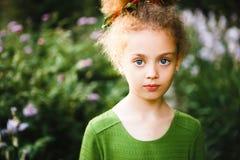 Een klein, krullend meisje in een groene kleding stock afbeeldingen
