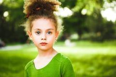 Een klein, krullend meisje in een groene kleding royalty-vrije stock foto