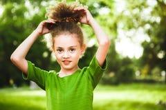 Een klein, krullend meisje in een groene kleding royalty-vrije stock fotografie