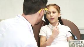 Een klein meisje is aan de tandarts gekomen en van een pijn in een tand geklaagd stock videobeelden