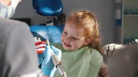 Een klein meisje als tandvoorzitter die aan de tandarts` s verklaringen luisteren over de aanstaande procedure om tanden te borst stock videobeelden