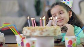 Een klein meisje bekijkt een cake met kaarsen en glimlacht stock video