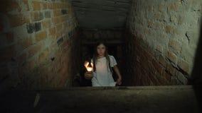 Een klein meisje beklimt op de stappen van de donkere kelder stock videobeelden