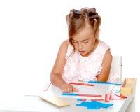 Een klein meisje bestudeert Montessori-materiaal Stock Foto