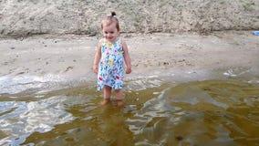 Een klein meisje bevindt zich in het water dichtbij de kust in een gebloeide kleding en is gelukkig stock video