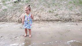 Een klein meisje bevindt zich op de holbank van de rivier in een gebloeide kleding en verheugt zich stock video