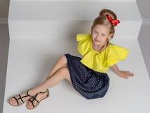 Een klein meisje bevindt zich op een witte trap Stock Foto
