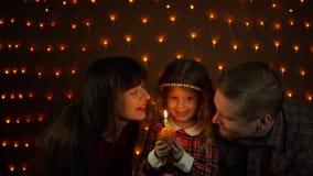 Een klein meisje blaast uit een kaars op een feestelijke cake met haar mamma en papa stock video