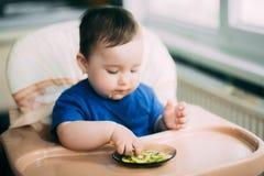 Een klein meisje in een blauwe t-shirtzitting in een kindzetel en het eten van een sinaasappel stock afbeelding