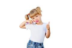 Een klein meisje borstelt haar tanden stock foto's