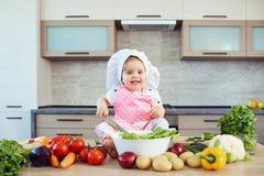 Een klein meisje in een chef-kokshoed treft in de keuken voorbereidingen royalty-vrije stock fotografie