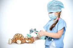 Een klein meisje in een chirurgisch kostuum maakt maskerventilatie aan haar stuk speelgoed tijger Stock Foto's