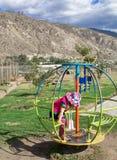 Een klein meisje in de hoed van Panama, die op de carrousel slingeren Achter het mooie landschap en de bergen De zomer royalty-vrije stock foto's