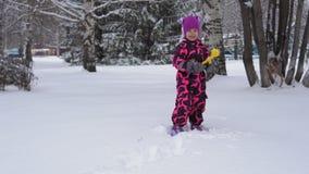 Een klein meisje in de roze winter jumpsuit spelen met sneeuw stock video