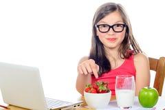 Een klein meisje die bij haar bureau zijn snack bekijken stock foto's