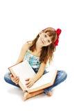 Een klein meisje die een boek op de vloer lezen stock foto's