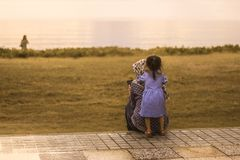 Een klein meisje die haar moeder koesteren stock fotografie