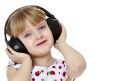 Een klein meisje die met hoofdtelefoons aan muziek luisteren Stock Foto's