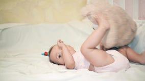 Een klein meisje die met een Teddybeer op een witte deken spelen stock footage