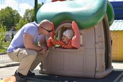 Een klein meisje die op de Speelplaats spelen, kijkt uit het weeshuis stock foto's