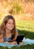 Een klein meisje die op het gras met haar tablet liggen Stock Afbeeldingen
