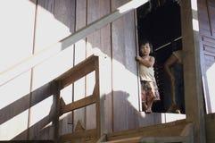 Een klein meisje die zich achter de deur in een dorp van Thailand bevinden Royalty-vrije Stock Foto