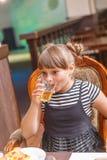 Een klein meisje drinkt sap van een glas bij een feestelijke lijst stock afbeeldingen