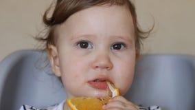 Een klein meisje eet een sinaasappel stock video