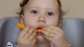 Een klein meisje eet een sinaasappel stock videobeelden