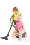 Een klein meisje en een kleine jongen door de Stofzuiger Stock Foto's