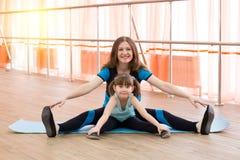 Een klein meisje en haar moeder doen sporten stock foto